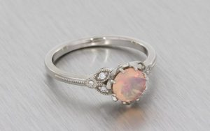 A Delicate And Vintage Inspired Palladium Engagement Ring Set With A Faceted Opal