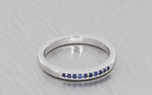 White gold wedding band set with blue sapphires and finished with beaded edges
