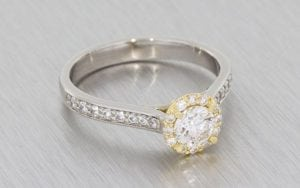 A Palladium Round Brilliant diamond halo ring housed in a 14k rose gold setting