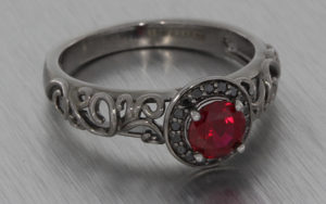 Black rhodium plated ring set with black diamonds and a round red ruby