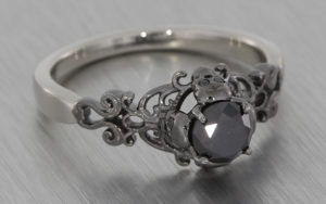 Gothic style ring set with black diamonds with scroll work and skull details