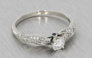 Platinum nature inspired engagement ring featuring a brilliant cut diamond with tourmaline peak stones