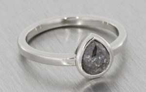 Platinum ring with a bezel set salt and pepper diamond