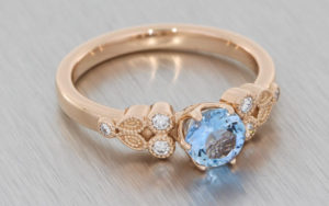 Rose gold ring set with an Aquamarine with small white diamonds and milgrain detailing
