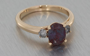 Trilogy ring crafted in 18k rose gold set with an oval Alexandrite with two smaller round salt & pepper diamonds on either side